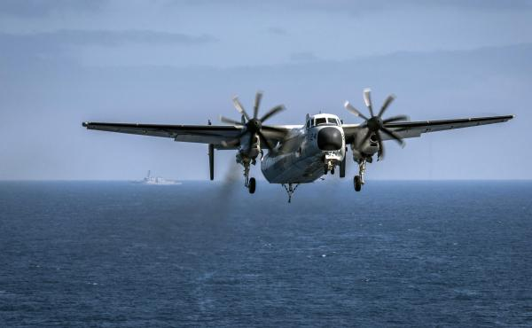 In this image provided by the U.S. Navy, a C-2A Greyhound prepares to land in August. Three remained missing after the same type of plane crashed Wednesday in the Philippine Sea.