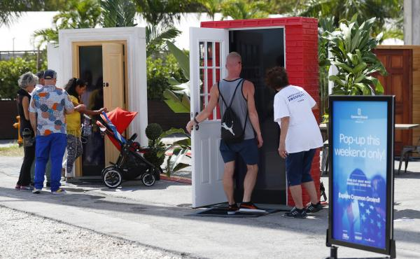 Passersby open doors to watch videos at an installation titled Common Ground, which shares personal stories of immigrants who are young entrepreneurs, war heroes and farmers in Miami on Oct. 3. The installation, organized by groups that get funding from t