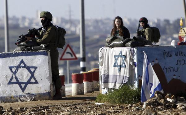 The U.N. Security Council has condemned Israel's construction of settlements, with Ambassador Samantha Power saying the project hurts Israel's security. In this photo from March, soldiers guard the Gush Etzion junction near a cluster of settlements in the