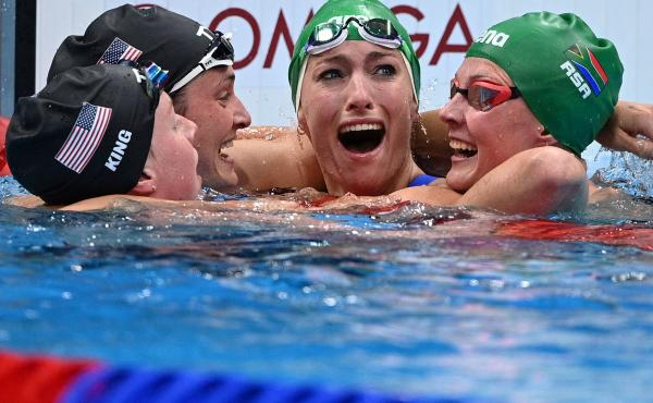 South Africa's Tatjana Schoenmaker, second from right, cheers with teammate Kaylene Corbett, right, and medalists Annie Lazor and Lilly King of Team USA after winning the final of the women's 200m breaststroke swimming event at the Tokyo Aquatics Centre o