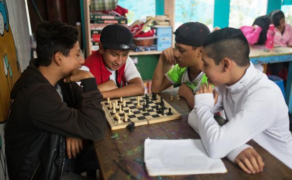 Teenagers play chess during a break at the main Los Patojos campus.
