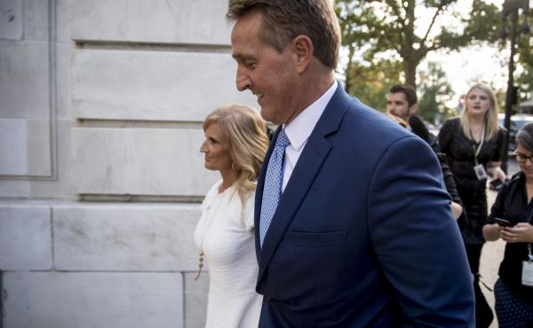 Sen. Jeff Flake, R-Ariz., accompanied by his wife Cheryl, leaves the Capitol in Washington on Tuesday after announcing he won't seek re-election in 2018.