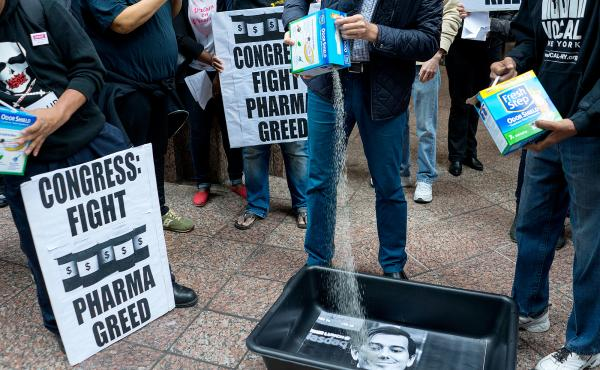 AIDS activists poured cat litter on an image of Turing Pharmaceuticals CEO Martin Shkreli during an October protest in New York.