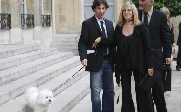 Barbra Streisand plays with her dog Samantha near her son, Jason Gould (left), and husband, James Brolin, in Paris in 2007. Samantha died last year, but Streisand now has clones of the dog.