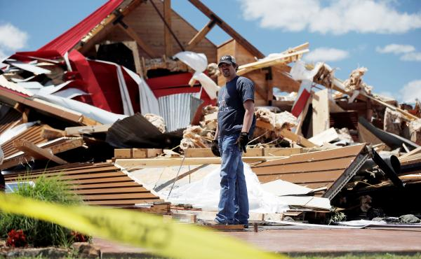 Kris Ingram, a DJ hired to perform at a prom at The Rustic Barn, looks through debris for his equipment after the event venue in Canton, Texas, sustained major tornado damage on Sunday.