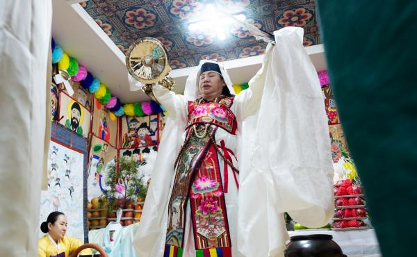 Shaman Jeong Soon-deok holds up a fan, bells and other ceremonial objects during an initiation ceremony at a temple in Seoul.
