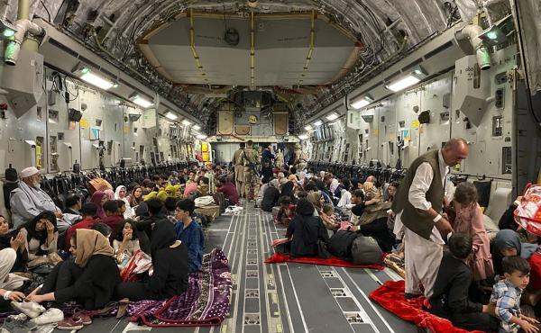 Afghans sit inside a U.S. military aircraft to leave Afghanistan at the military airport in Kabul Thursday after the Taliban's takeover of the country.