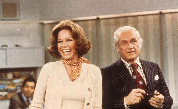 Actors Mary Tyler Moore and Ted Knight laugh in a still from The Mary Tyler Moore Show in 1976.