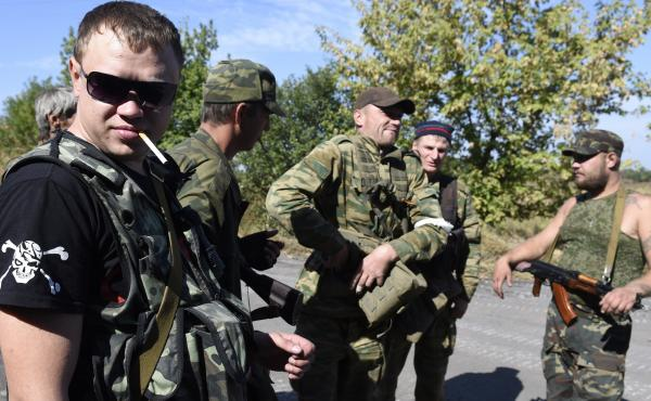 Pro-Russian militants take a break at a checkpoint close to where shelling continued Sunday between pro-Russian forces and the Ukrainian army in the village of Olenivka, some 30 kms south of Donetsk on the way to Mariupol, eastern Ukraine.