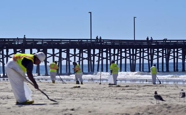 Workers clean oil from the sand, south of the pier, in Newport Beach, Calif., Tuesday, Oct. 5, 2021. A leak in an oil pipeline caused a spill off the coast of Southern California, sending about 126,000 gallons of oil into the ocean, some ending up on beac