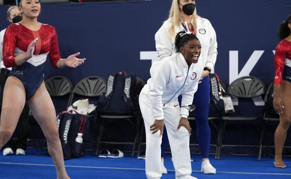 Simone Biles (center) cheers the performance of teammate Grace McCallum after she withdrew from the artistic gymnastics women's final at the Summer Olympics on Tuesday in Tokyo.