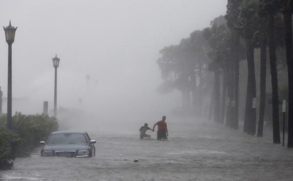 Pedestrians walk on a flooded street on Sept. 11 as tropical storm Irma hits Charleston, S.C.