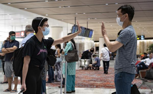 New arrivals greet each other without touching at Changi Airport earlier this week in Singapore. The island country, which imposed a ban on short-term visitors shortly after this photograph was taken, has now also implemented the threat of prison time for