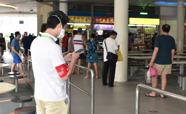 A safe-distancing enforcement officer wearing a red armband checks his phone at a food court in Singapore on Saturday. The officers have been deployed to ensure people maintain distance from one another, as Singapore grapples with a spike in coronavirus c