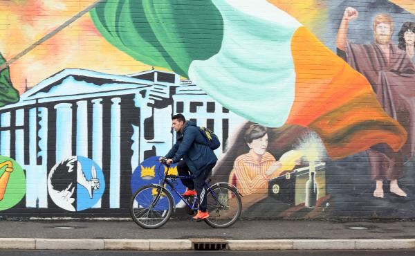 A cyclist rides past a mural on the Catholic Falls Road in Belfast, Northern Ireland, on Saturday after results were finalized in the province's snap election.