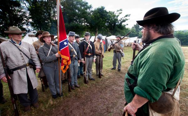 Waverly Adcock, a sergeant and founder of the West Augusta Guard, prepares his company for inspection and battle at a Civil War re-enactment in Virginia. Sara Smith, whose great-great-grandfather was wounded at the Battle of Gettysburg, holds the Confeder