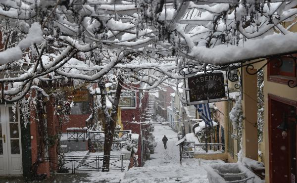 People make their way through the popular tourist area of Plaka during a heavy snowfall in Athens on Tuesday.