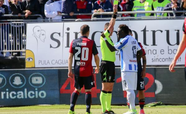 After Sulley Muntari (right) heard racial slurs from fans during a match in Sardinia, Italy, on April 30, he protested — and got a yellow card from the referee. A supporter holds the card aloft.