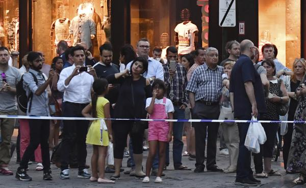 People stand behind police tape as they are evacuated at the Grand Place near Central Station in Brussels after an explosion on Tuesday.