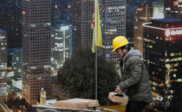A worker loads building material on a cart outside a construction site at the Central Business District in Beijing. China's top economic planner expressed confidence this month that stronger consumer spending will help the economy grow.