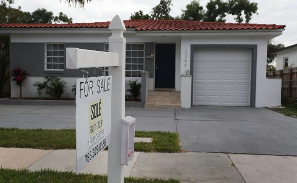 "A ""for sale"" sign is seen in front of a home in Miami on Jan. 24, 2018. The partial shutdown of the federal government is causing some financial problems for furloughed workers who can't refinance their mortgages or buy homes because lenders can't verify"
