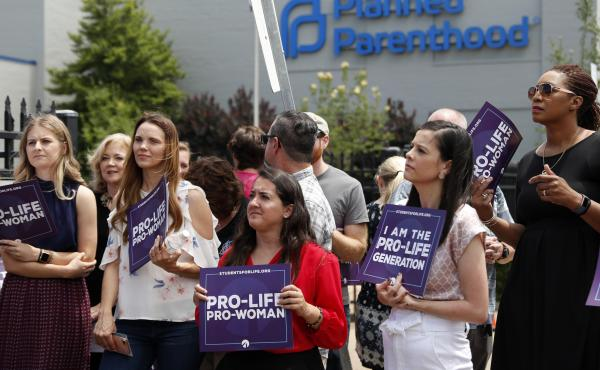 Anti-abortion-rights advocates gather outside a St. Louis Planned Parenthood clinic in June. Title X recipients have been given more time to comply with new regulations.