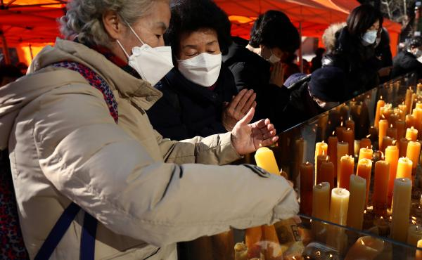 South Koreans pray for their children taking the College Scholastic Ability Test at Chogey temple in Seoul on Thursday. New coronavirus infections in the country have spiked in recent days.