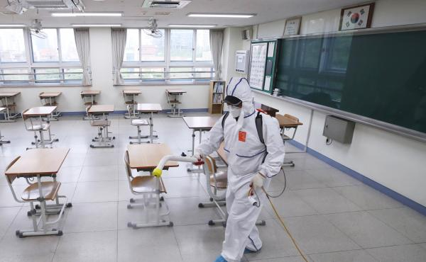 A person sprays disinfectant at a high school amid the coronavirus outbreak on Monday, in Seoul, South Korea.