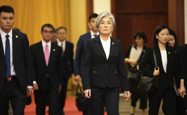 South Korea has announced it will withdraw from a 2016 military intelligence-sharing pact with Japan. Here, South Korean Foreign Minister Kang Kyung-wha, center, and Japanese Foreign Minister Taro Kono, trailing at left, walk in Beijing's Great Hall of th