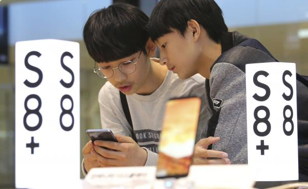 Students try out a Samsung Electronics Galaxy S8 Plus smartphone at a shop in Seoul, South Korea, on April 27. Many post-college grads in South Korea spend years studying for tests in the hopes of winning a job at a company like Samsung.