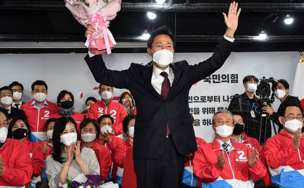 Oh Se-hoon (center), the mayoral candidate of the main opposition People Power Party, holds flowers as he celebrates with party members after exit polls showed he would win.