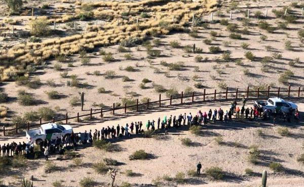 Migrants line up after being apprehended along the U.S.-Mexico border near Lukeville, Ariz. Mexico is at the top of the image, beyond the border fence.