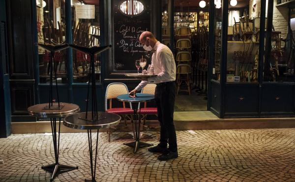 A waiter closes a bar terrace in Paris earlier this month amid a surge in coronavirus cases.