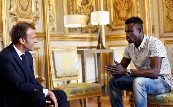 "French President Emmanuel Macron speaks with Mamoudou Gassama at the presidential palace in Paris, on Monday. Macron offered Gassama citizenship for his ""heroic act"" in saving a four-year-old."