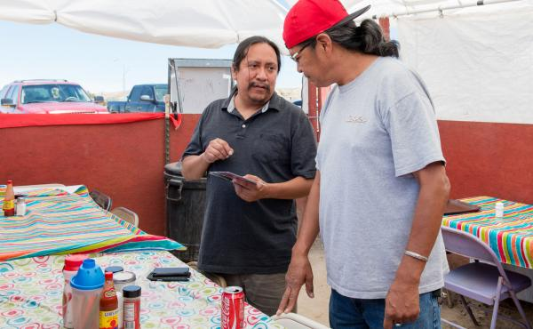 Outreach coordinator Sonny Weahkee (left) talks with a restaurant customer about health insurance for Native Americans in Shiprock, N.M., in early August.