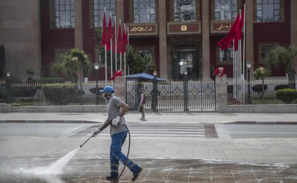A worker disinfects a main avenue outside the parliament building in a bid to prevent the spread of coronavirus on Wednesday in Rabat, Morocco. The country imposed sudden, sweeping restrictions on travel.