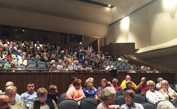 A few hundred people gather in an auditorium at Hutchinson Community College in Hutchinson, Kan., to watch the state Supreme Court hear oral arguments.