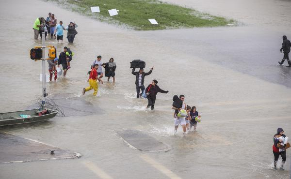 People walk down a flooded street as they evacuate their homes in Houston, Texas, on Monday.