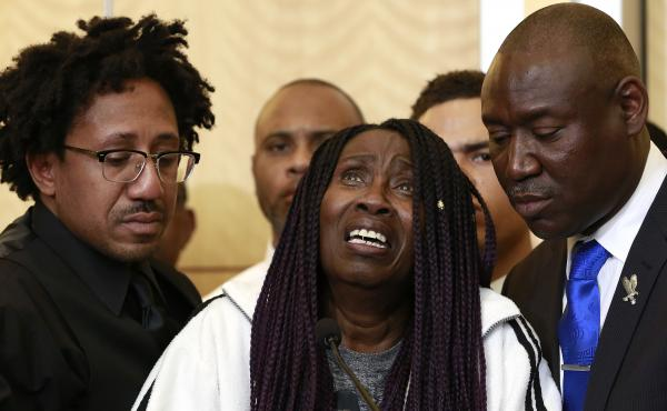 A tearful Sequita Thompson pleads for police officers who killed her unarmed grandson, Stephon Clark, to face criminal charges. Thompson was accompanied at a news conference by Clark's uncle, Kurtis Gordon (left) and attorney Ben Crump (right).