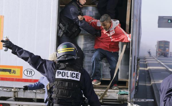 French riot policemen force out migrants who were hidden in a truck that was making its way to the ferry terminal in Calais in western France on Wednesday. The cross-Channel port has become the last barrier for economic and political migrants trying to en