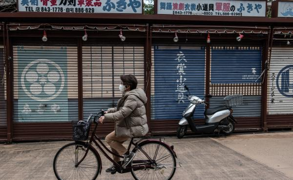 A woman wearing a face mask cycles past closed souvenir shops near Sensoji Temple, normally a popular tourist destination, on Feb. 2 in Tokyo. Prime Minister Yoshihide Suga announced a one-month extension to the state of emergency across much of the count