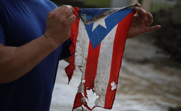 Jose Javier Santana says this torn and frayed Puerto Rican flag is representative of the state of the island now — eight months after Hurricane Maria hit.