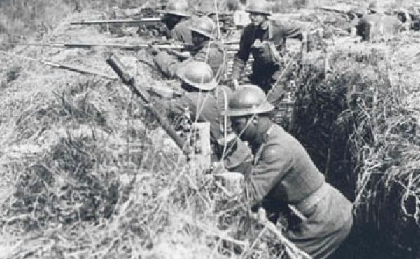 """Soldiers of the 369th Infantry practice in France during World War I. They are wearing French """"Adrian"""" helmets and using French issued rifles and equipment."""