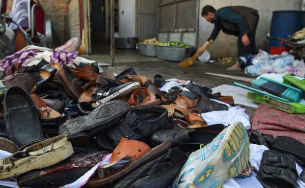 A man cleans an area next to a pile of victims' shoes outside a wedding hall after a deadly suicide bomb blast on Saturday night in Kabul, Afghanistan.