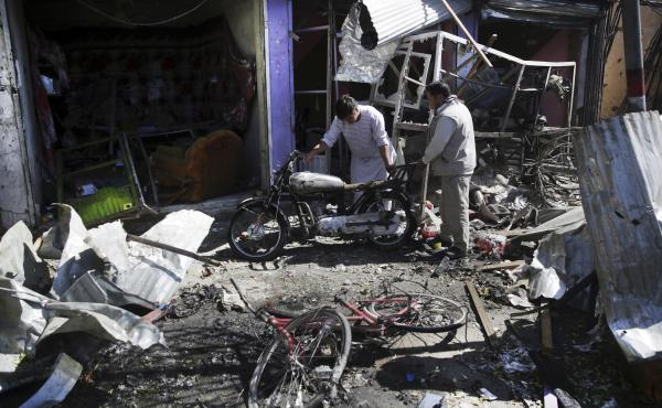 Men look at the remains of their properties at the site of a suicide attack in Kabul, Afghanistan, Monday, July 24, 2017. A suicide car bomb killed dozens of people as well as the bomber early Monday morning in a western neighborhood of Afghanistan's capi