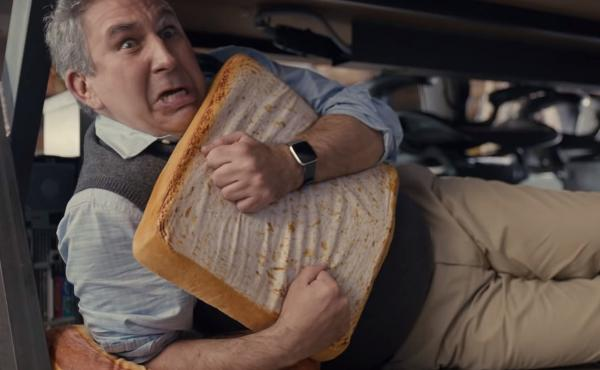 A man cowers under a desk, hugging a pillow shaped like a slice of bread, in a scene from a  Little Caesars commercial that ran during the 2020 Super Bowl.