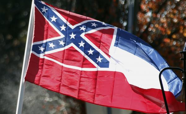 A state flag of Mississippi is unfurled by Sons of Confederate Veterans and other groups in 2016 on the grounds of the state Capitol in Jackson, Miss.