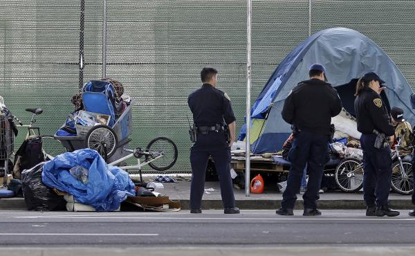 San Francisco police officers wait while homeless people collect their belongings. Nearly a quarter of the country's homeless population lives in California.