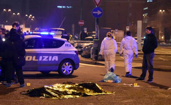 "A body is covered with a thermal blanket after a shootout between Italian police and a man near a train station in Milan's Sesto San Giovanni neighborhood early Friday. Italy's interior minister said the man killed is ""without a shadow of doubt"" Anis Amri"