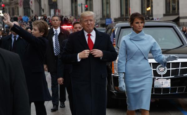 Barron Trump (left) waves as his mother and father walk the parade route after Donald Trump was sworn in as president Friday. A Saturday Night Live writer's tweet that mocked the 10-year-old has resulted in her indefinite suspension.